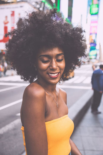 Shy young woman with afro hairstyle standing on city street