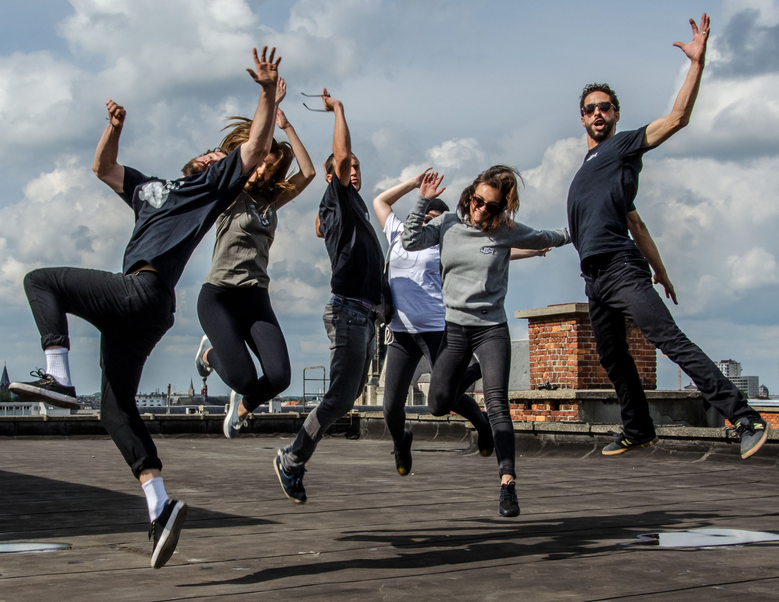 jumping, full length, motion, leisure activity, mid-air, sky, vitality, dancing, real people, outdoors, day, lifestyles, enjoyment, casual clothing, fun, cloud - sky, skill, low angle view, men, smiling, togetherness, happiness, friendship, energetic, breakdancing, young adult