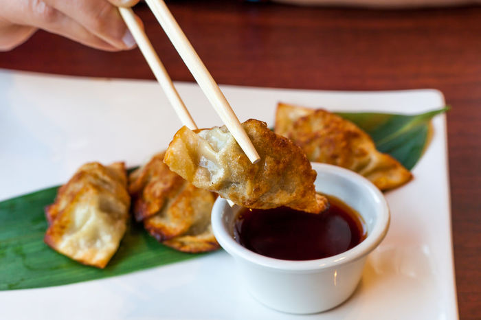 Eating pot stickers with chopsticks Chinese Food Pot Stickers Asian Food Bowl Chopsticks Dipping Sauce Finger Food Food And Drink Food On Leaf Freshness Fried Hand Holding Human Hand Japanese Food Meal One Person Plate Ready-to-eat Sauce Soy Sauce Table Temptation Tray