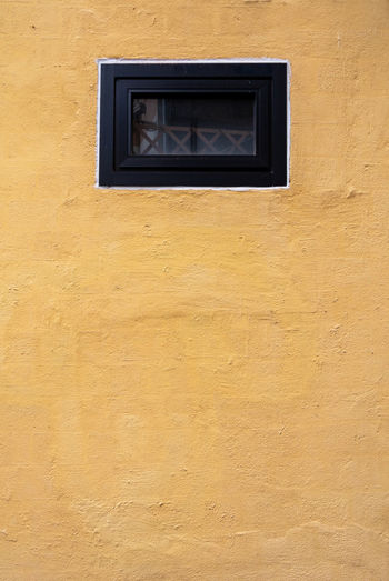 The yellow cement concrete wall and window