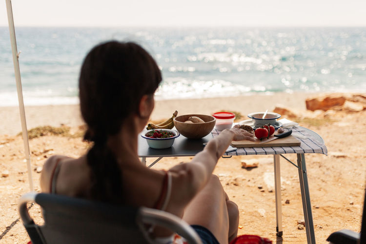 Rear view of woman sitting by food on table at beach
