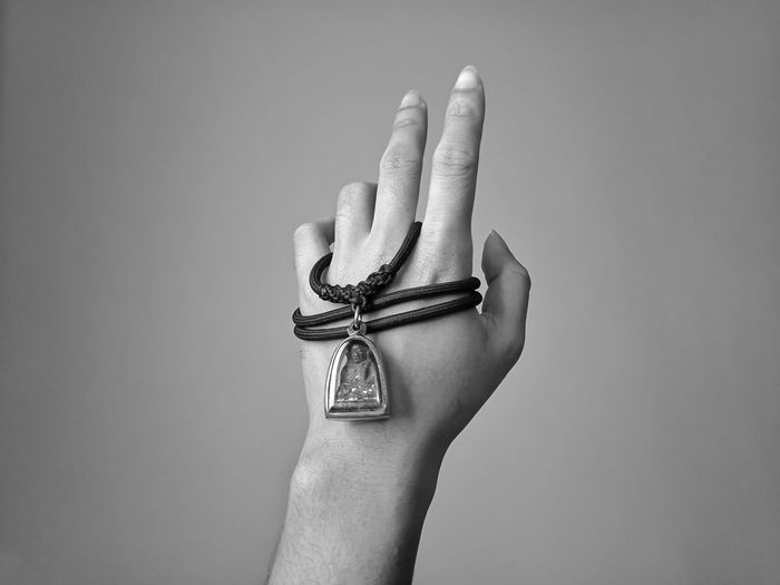 Close-up of human hand with locket against gray background