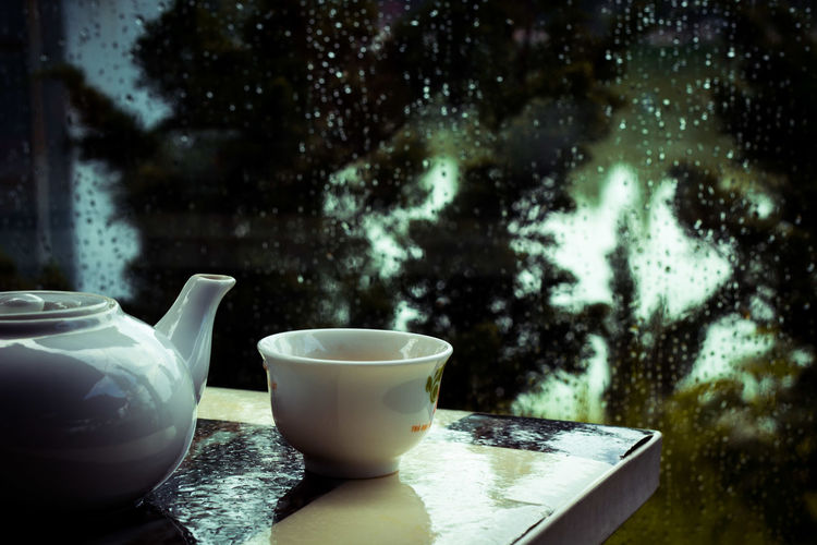 Close-up of teapot with cup on table against wet window
