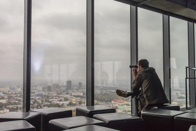 Man Looking At Cityscape Through Binoculars While Sitting At Office