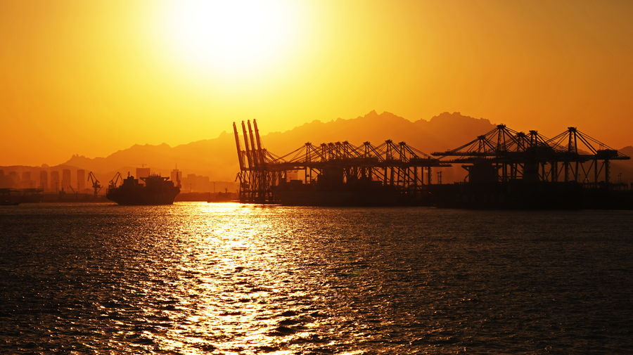Silhouette cranes at commercial dock by sea against orange sky