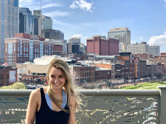 Portrait of smiling young woman standing against buildings in city