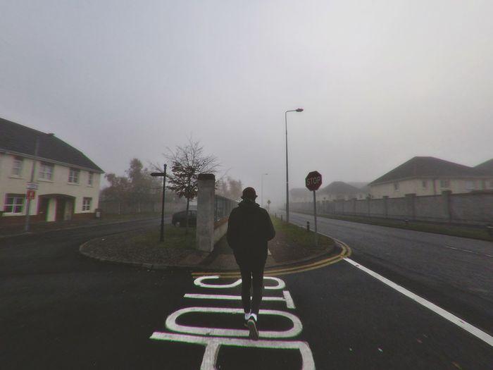 Man walking on road against sky