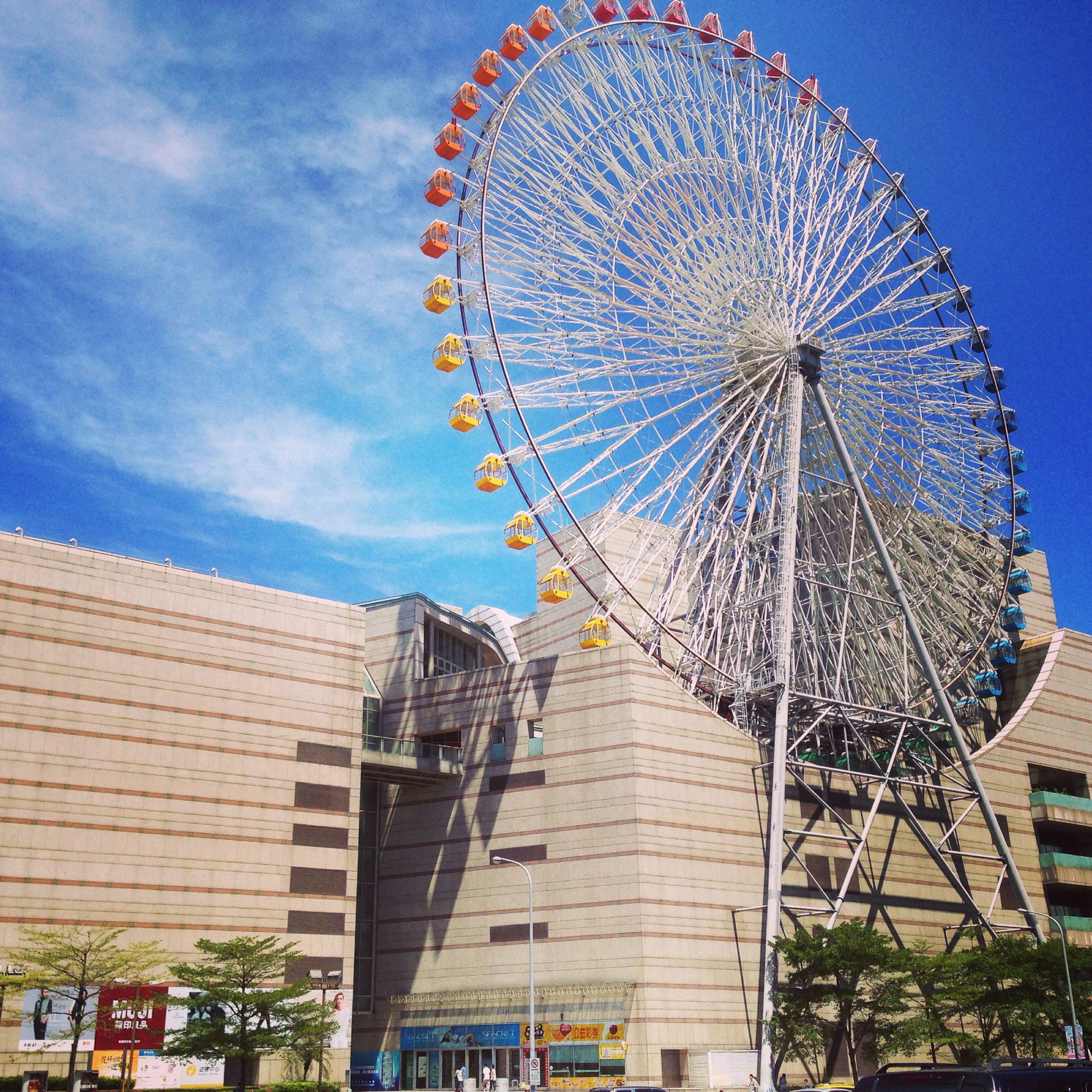 low angle view, built structure, architecture, ferris wheel, amusement park, arts culture and entertainment, building exterior, sky, amusement park ride, blue, day, outdoors, no people, cloud - sky, cloud, sunlight, large, clear sky, tall - high, metal