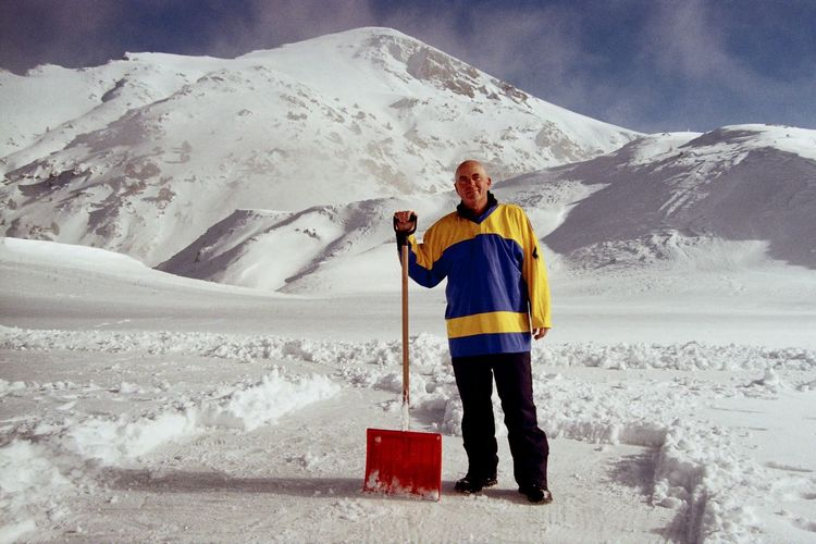 Portrait of man with shovel on snow covered land