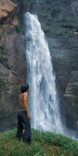 Full length of shirtless man standing in water