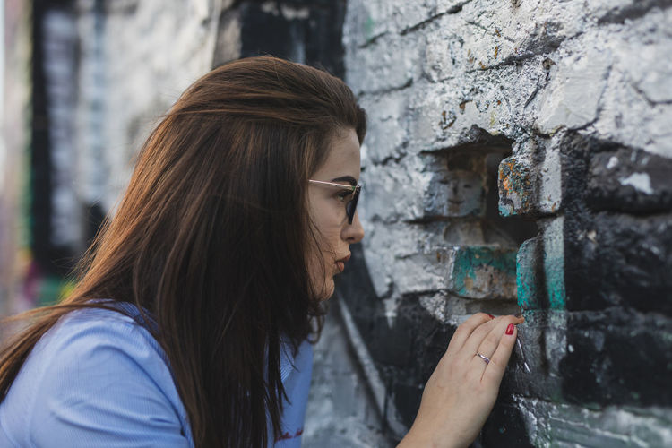 Side view of young woman looking through hole in wall