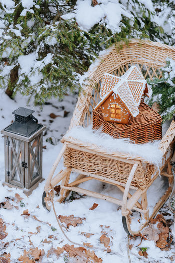 Gingerbread house on a sled in the winter snow-covered forest Seat Chair Nature Snow Tree No People Winter Table Day Cold Temperature Plant White Color Wicker Field Wood - Material Land Outdoors Basket Focus On Foreground Gingerbread Forest Sled Christmas Decoration