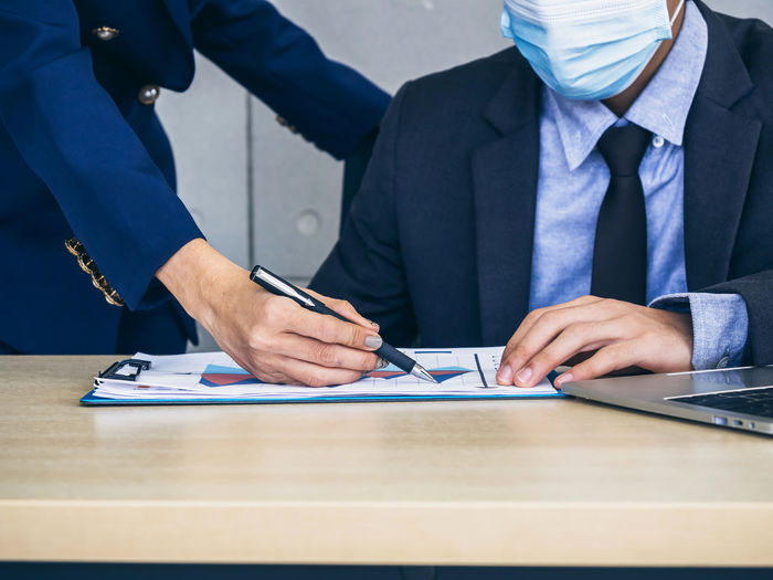 Midsection of business people wearing flu mask brainstorming at office