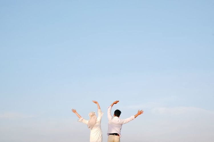 Rear view of woman with arms raised against clear sky