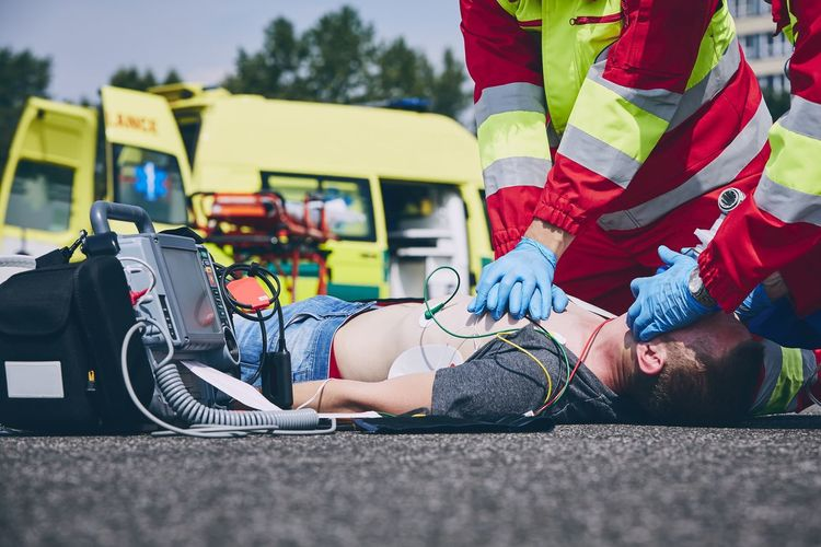 Midsection of paramedic giving cpr to unconscious man lying on street