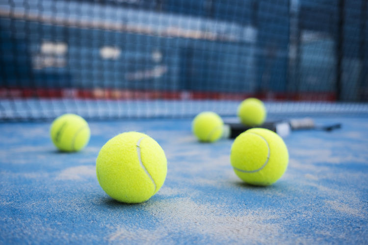 """Paddle tennis racket and balls on court artificial grass. """"PADDLE TENNIS"""" KEY WORD Play Artificial Grass Balls Blue Concrete Court Equipment Fence Game Indoor Net Nobody Outdoors Paddle Paddle Tennis Paddle-tennis Padel Racket Racquet Recreation  Sport Still Life Tennis Match"""