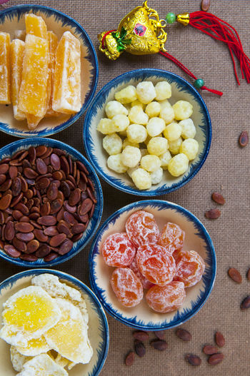 Directly above view of food in bowls with scattered seeds on table