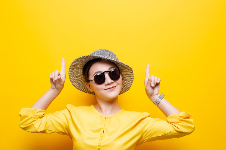 Portrait woman wearing sunglasses and hat point up to copy space isolated over yellow background Yellow Yellow Background One Person Fashion Arms Raised Sunglasses Summer Summertime Hat Glasses Happy Bright Hipster Makeup Colors Spring Posing Colorful Wear Trend Popular Color Model Day Sunny Woman Isolated Female Asian  Lifestyle Happiness Travel Relax Relaxing Relaxation Attractive Vacation Vacation Time Cheerful Positive Smile Positive Emotion Copy Space Sun Hat Leisure Activity Leisure Point Pointing Up Finger
