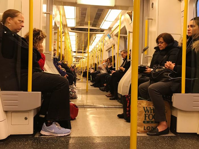 Sitting Indoors  Young Adult Real People Young Women Communication Full Length Lifestyles Leisure Activity Wireless Technology Standing Day Occupation Technology Friendship Adult People Adults Only Tube Station  London Underground