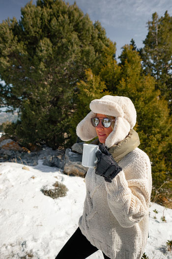 Full length of woman wearing sunglasses in park during winter