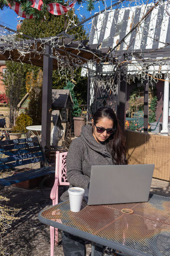 Woman using laptop on table at cafe