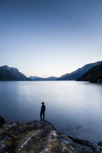 Silhouette Man Standing On Cliff By Lake Against Sky