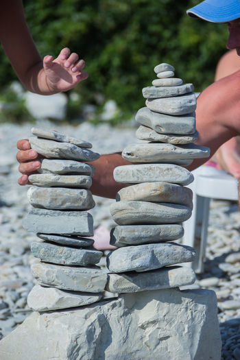 the towers of pebble stones on the beach, games on the beach Human Hand Stack Hand Focus On Foreground Human Body Part Day Real People One Person Body Part Balance Human Finger Finger Close-up Outdoors Solid Holding Unrecognizable Person Nature Stone - Object