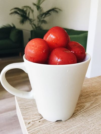 Close-up of tomatoes in cup on table at home