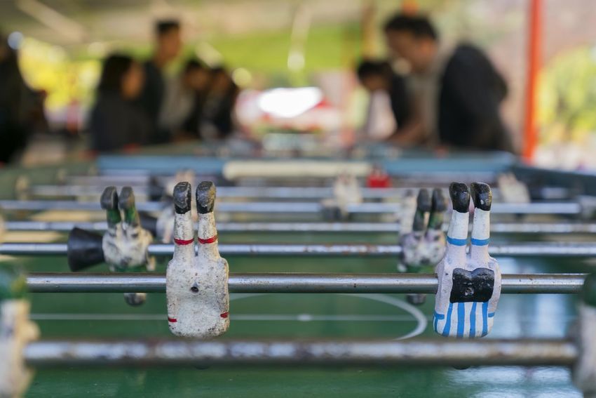 Close up of a soccer table installed in a public square. Focus On Foreground Metal Close-up Incidental People Day Leisure Activity Human Representation Selective Focus Soccer Leisure Games Relaxation Representation Sport Outdoors Team Sport Competition Male Likeness Real People People Group Of People