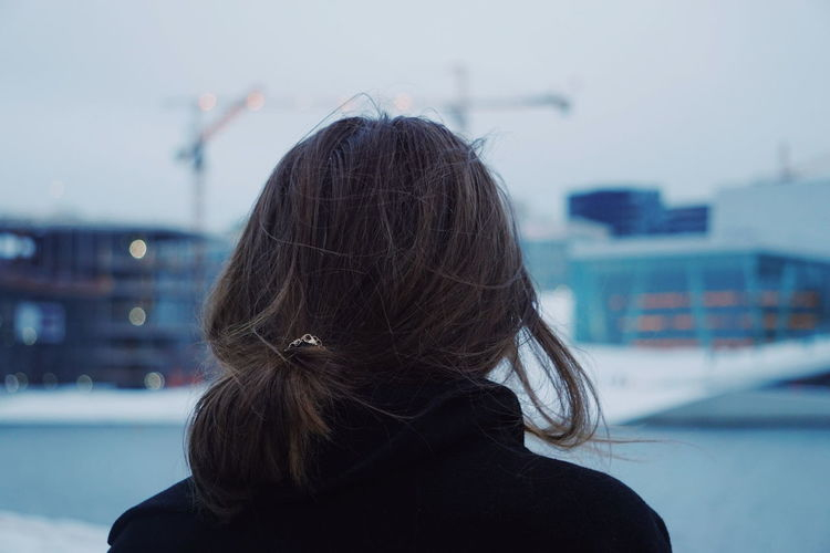 Rear view of woman against sky during winter