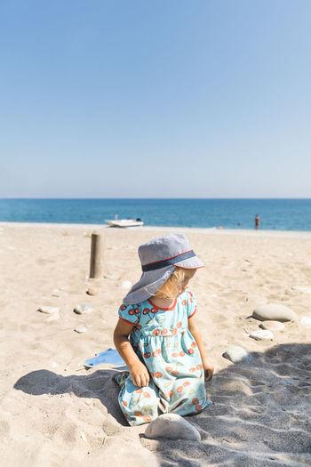 Girl sitting on sand at beach against clear sky