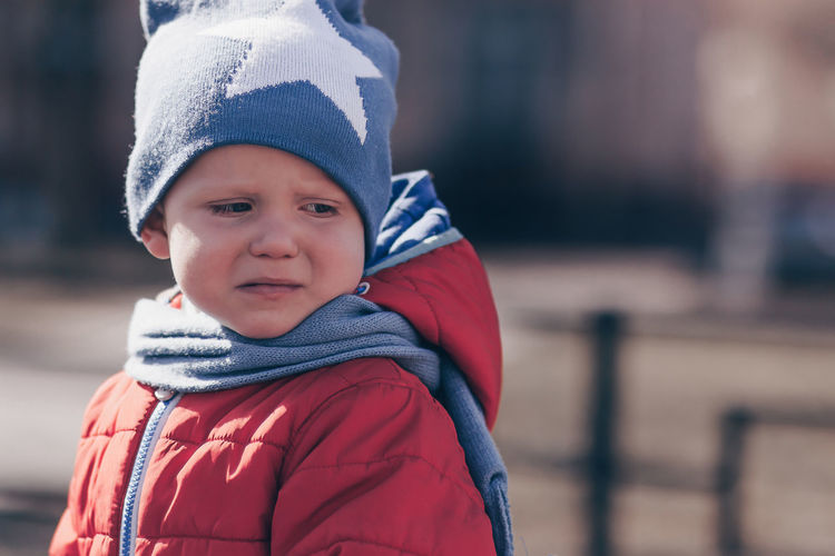 Close-up of crying boy wearing warm clothing during winter