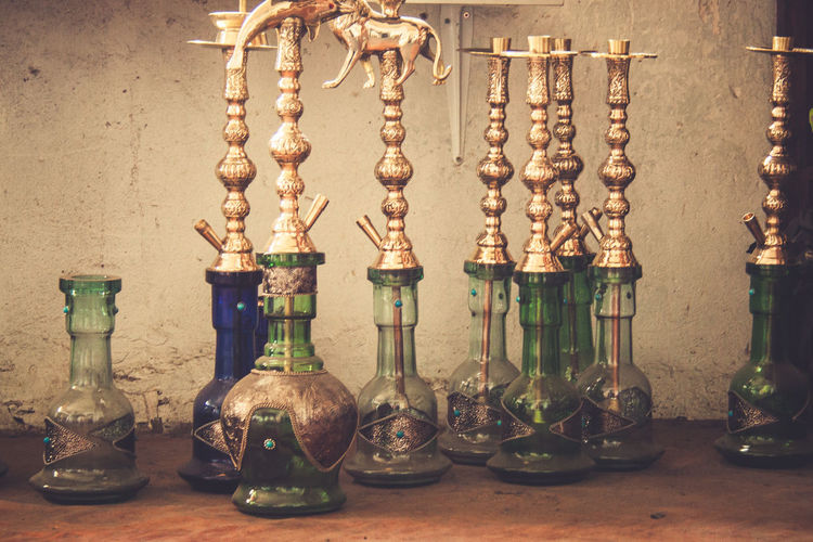 Close-up of glasses on table against wall