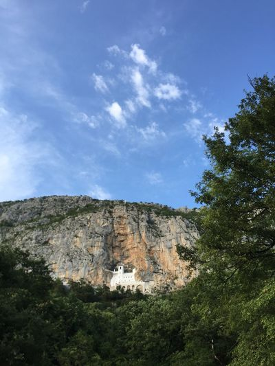 Distant view of ostrog monastery by rock formations against sky