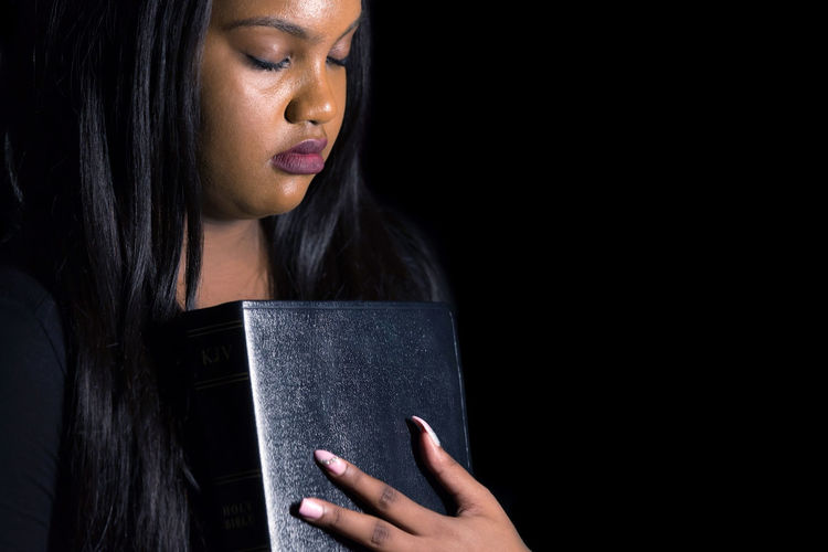 Close-up of young woman praying against black background