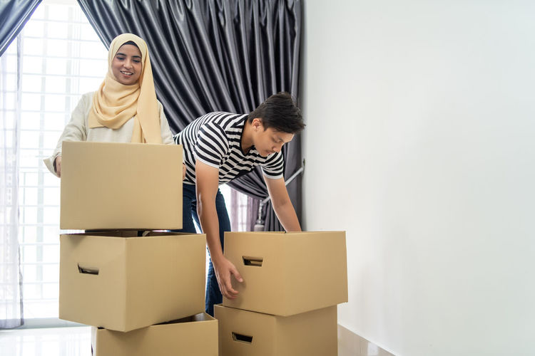 asian couple moving out and moving in into new house Adult Beginnings Box Box - Container Cardboard Cardboard Box Casual Clothing Couple - Relationship Emotion Happiness Home Ownership Indoors  Men Moving House Packing Smiling Standing Teamwork Two People Women Young Adult Young Men Young Women