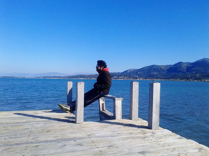 Side view of man sitting on pier over sea against clear blue sky