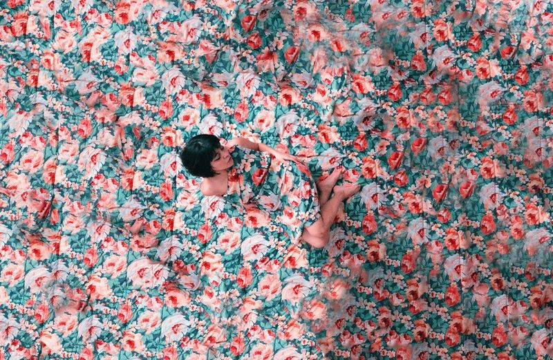 High angle view of woman lying down on floral background