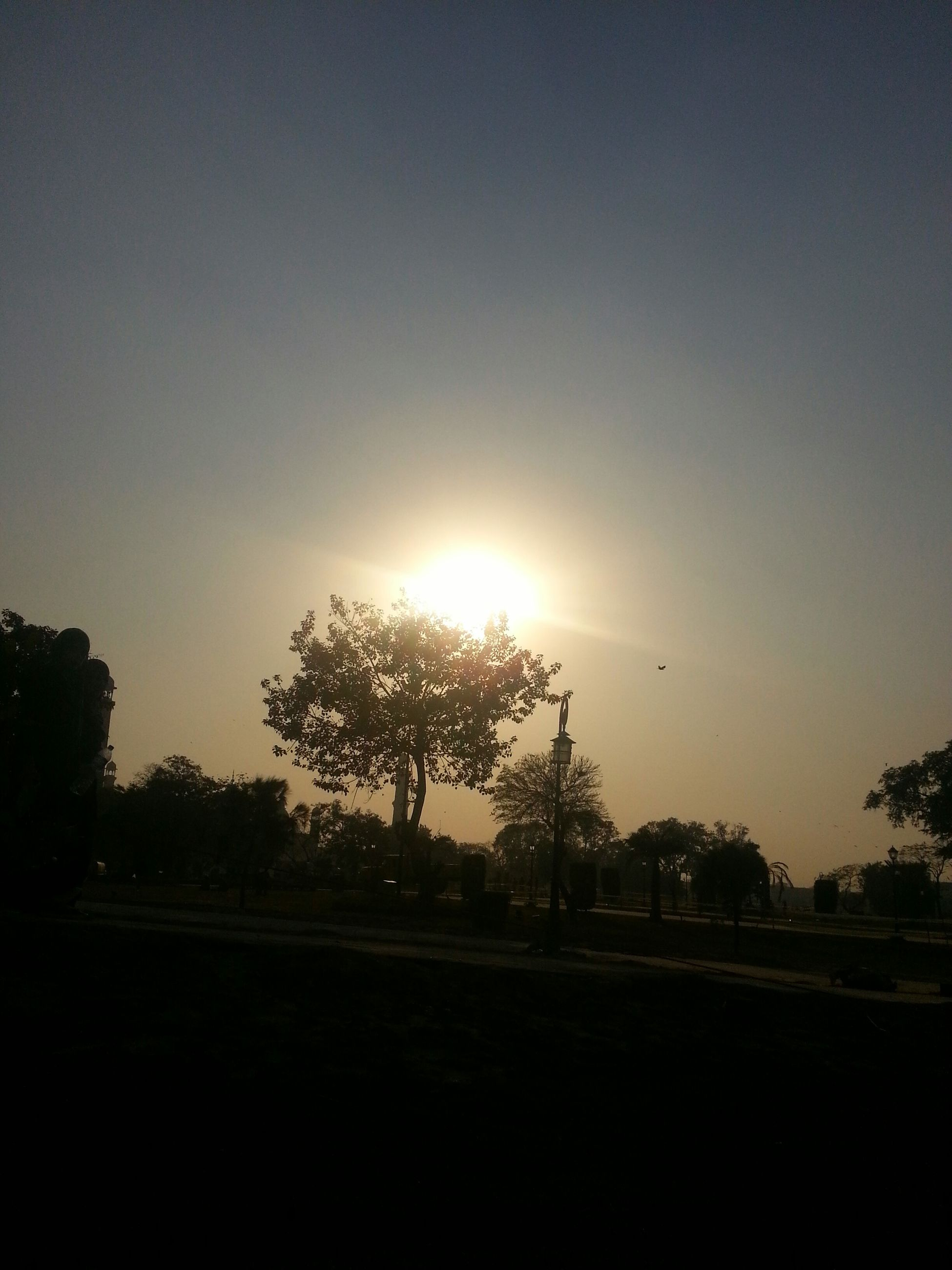 sunset, sun, sunlight, car, sky, tree, nature, silhouette, no people, road, sunbeam, beauty in nature, outdoors, day