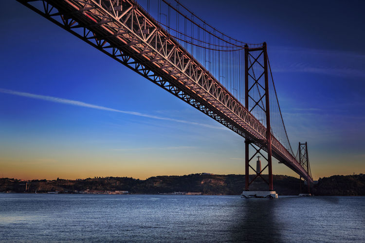 The Ponte 25 de Abril Bridge in Lisbon, Portugal Architecture Bridge - Man Made Structure Built Structure City, Ponte 25 De Abril Bridge, Sintra, Architecture, Atlantic, Blue, Bridge, Coast, Europe, Evening, Famous, Holiday, Landmark, Landscape, Lights, Lisboa, Lisbon, Metal, National, Night, Outdoor, Palace, Park, Portugal, River, Sea, Sky, Summer, Tagus, Te Connection Day Nature No People Outdoors Sky Transportation Water