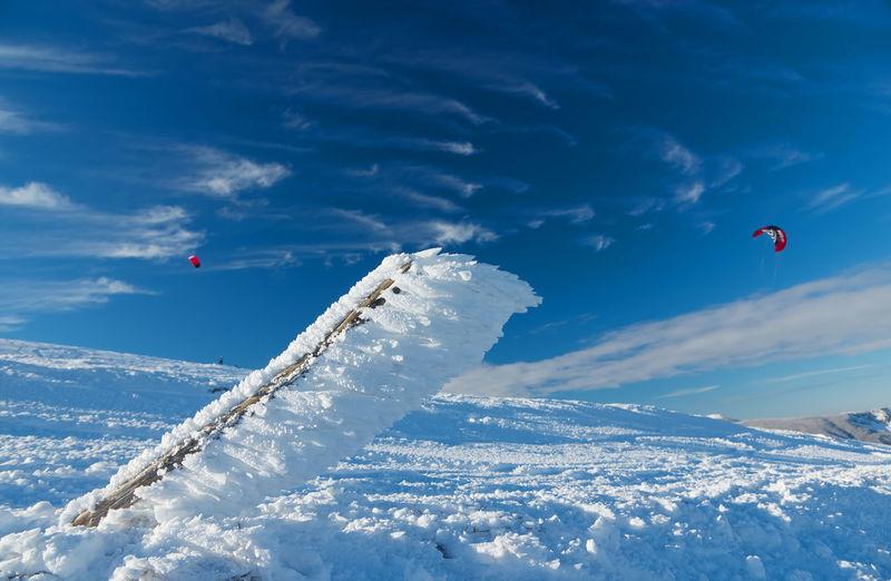 People flying kite in snow against sky