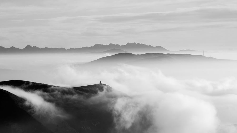 Scenic view of mountains in foggy weather against sky