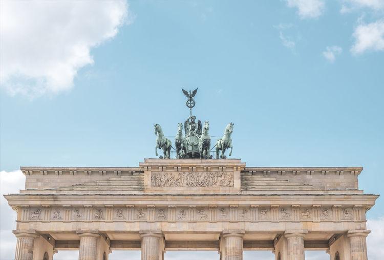 Brandenburg gate with quadriga statue against blue sky