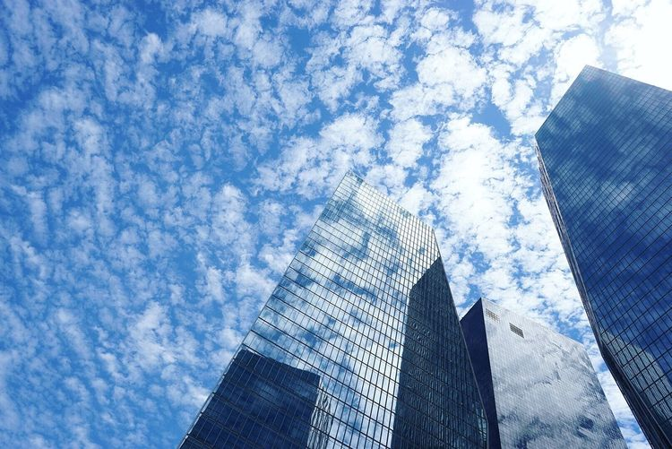 Low angle view of tall buildings against clouds