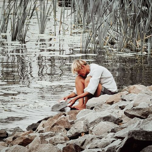 Woman sitting on rock at shore