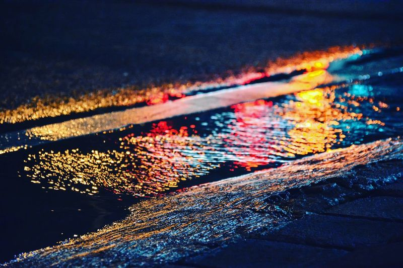 Reflection of city lights on puddle