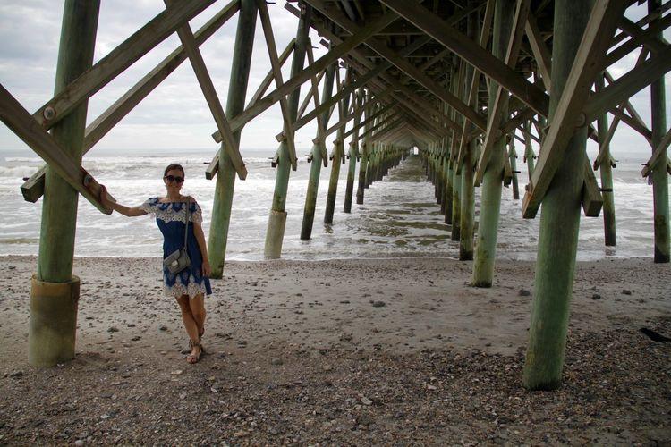 Portrait of woman standing under pier at beach