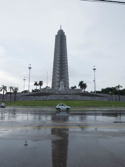 View of monument in city against cloudy sky