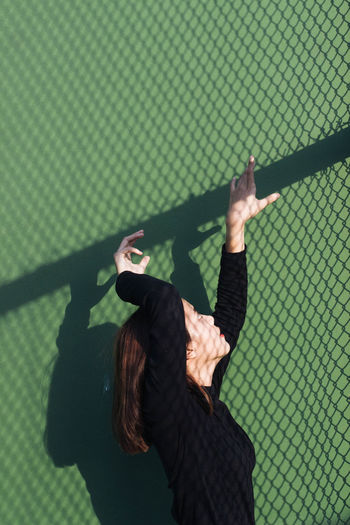 young woman wearing black shirt arm raised trying to climb the wall with net shadow reflect Adult Adults Only Arms Raised Climb Day Indoors  One Person People Real People Reflection Shadow Standing Women Young Adult