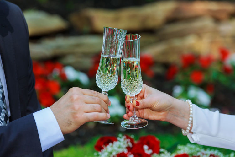 Cropped Hand Of Groom Toasting Champagne Flute To Bride During Wedding Ceremony